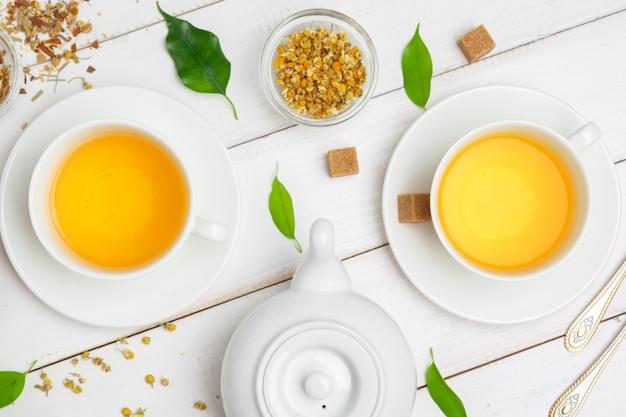 Czajnik i filiżanki herbaty na białym drewnianym