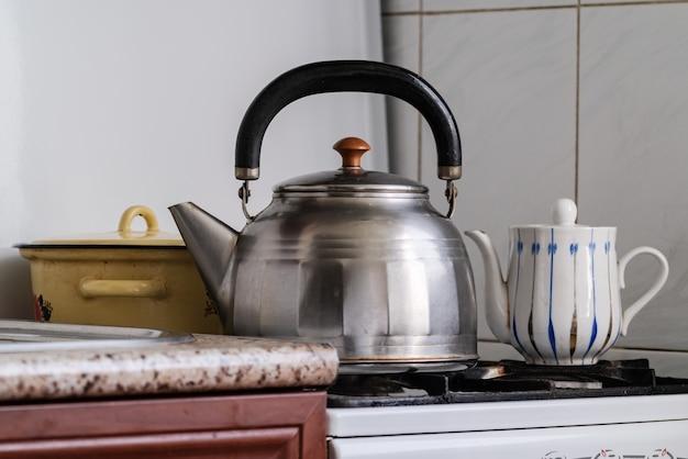 Czajnik i garnek na kuchence gazowej, parzenie herbaty