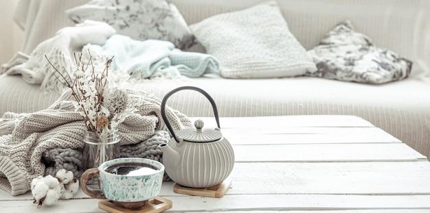 Czajnik i piękny ceramiczny kubek z detalami dekoracyjnymi w salonie w stylu hygge