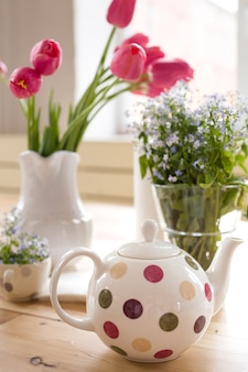 Czajnik w kropki i wazony z pięknymi wiosennymi zapomnieniami i kwiatami tulipanów na drewnianym stole
