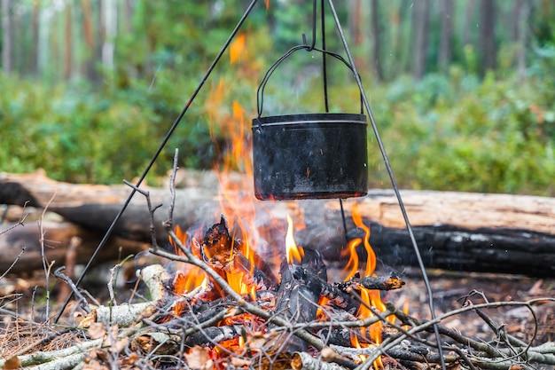 Czajnik wiszący nad ogniem. gotowanie żywności w ogniu na wolności. podróże, koncepcja turystyki. zdjęcie stockowe