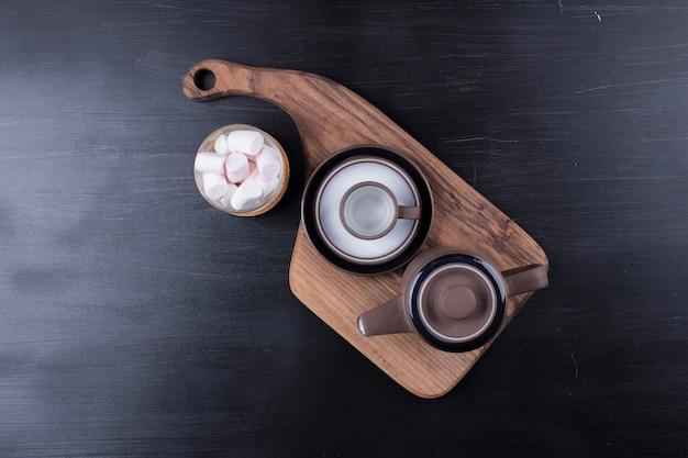 Czajnik z filiżanką i piankami na drewnianym talerzu, widok z góry.