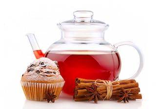 Czajnik z herbatą, przyprawami i ciastem na białym tle