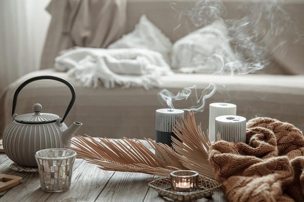 Czajnik z herbatą i świecami na stole we wnętrzu pokoju