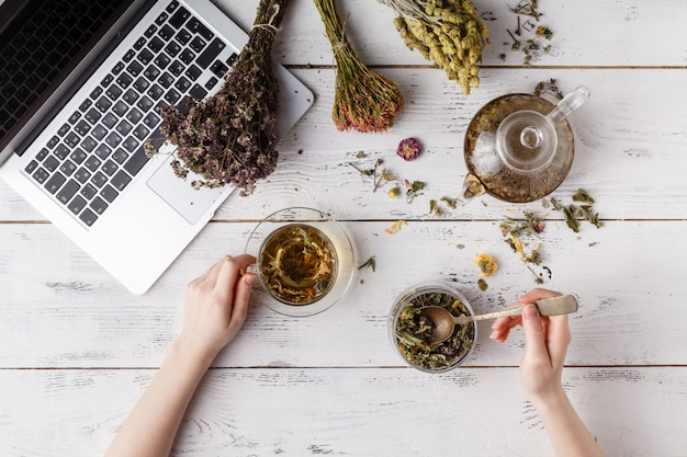 Czajnik z herbatą ziołową na stole w kuchni i kobieta pisze przepis