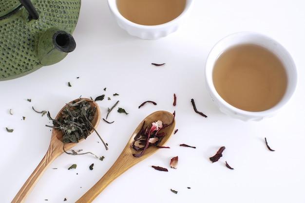 Czajnik żelazny filiżanki drewniana łyżka liście herbaty suszony hibiskus białe tło