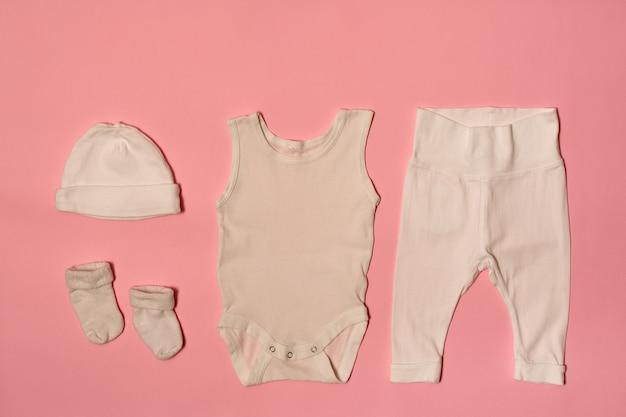 Czapka, body, spodnie i skarpetki na różowej powierzchni