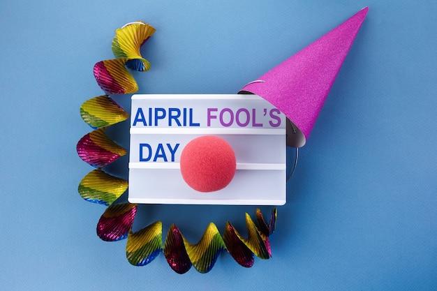 Czapka imprezowa i podświetlane pudełko z frazą prima aprilis na niebieskim tle