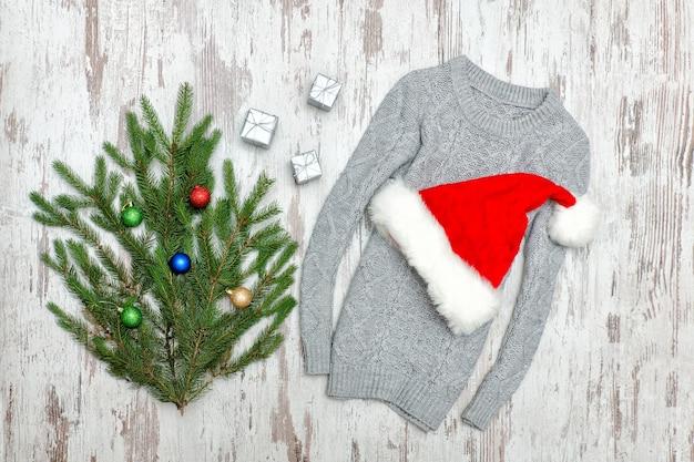 Czapka mikołaja na szarym swetrze. zdobiona gałąź jodły. drewniane tło. modna koncepcja