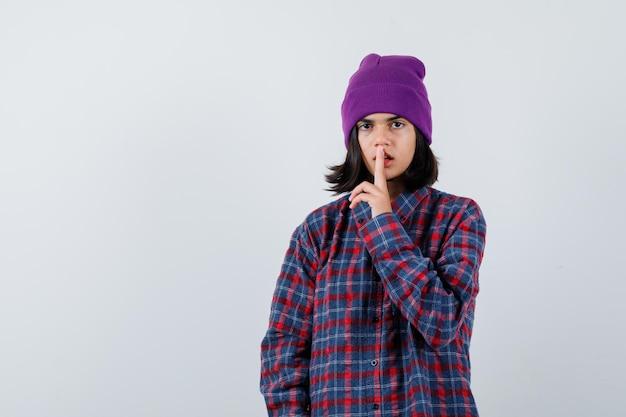 Czapka nastoletnia kobieta pokazująca gest ciszy, patrząc ostrożnie