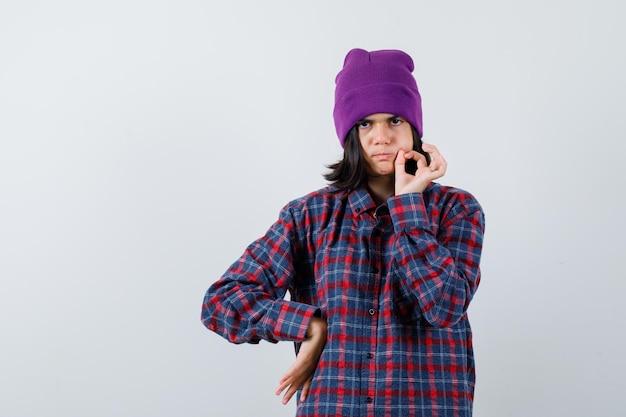 Czapka nastoletnia kobieta pokazująca gest zip wygląda poważnie