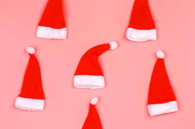 Czapka świętego mikołaja na różowym tle. minimalistyczne świąteczne skandynawskie tło z pustym miejscem na tekst