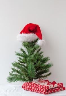 Czapka świętego mikołaja nakładana jest na małą sztuczną choinkę, a obok leży świąteczny sweter...