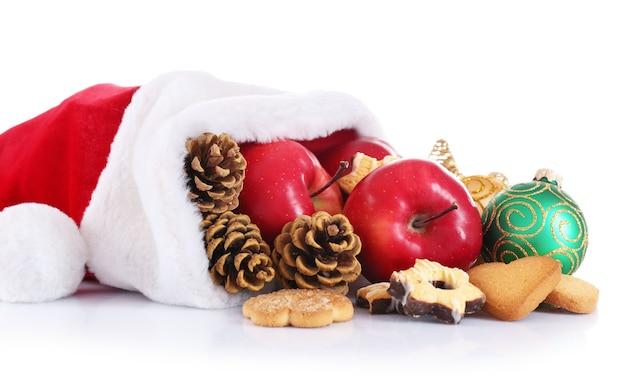 Czapka świętego mikołaja wypełniona prezentami świątecznymi, na białym tle