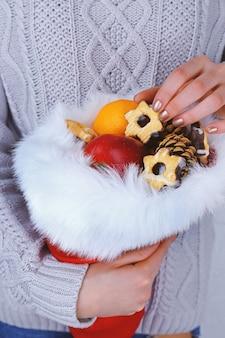 Czapka świętego mikołaja wypełniona prezentami świątecznymi w rękach kobiety