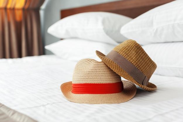 Czapka wakacyjna na łóżku w hotelu.