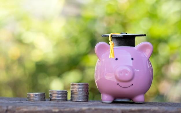 Czapki absolwentów umieszczone na skarbonkach i monety ułożone na drewnianej podłodze.