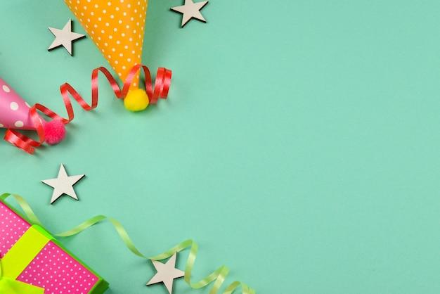 Czapki urodzinowe i prezent, konfetti na zielonym tle. miejsce na tekst lub projekt.