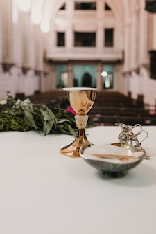 Czara wina na stole podczas weselnej mszy ślubnej. koncepcja religii. katolickie ozdoby eucharystyczne do sprawowania eucharystii