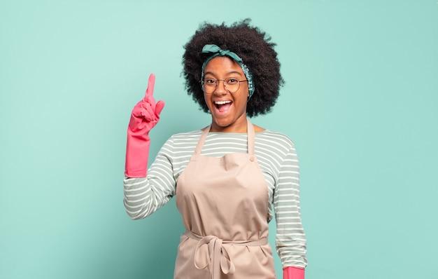 Czarna afro kobieta czująca się jak wesoła i podekscytowana geniusz po zrealizowaniu pomysłu, radośnie unosząca palec, eureka !. koncepcja sprzątania .. koncepcja gospodarstwa domowego