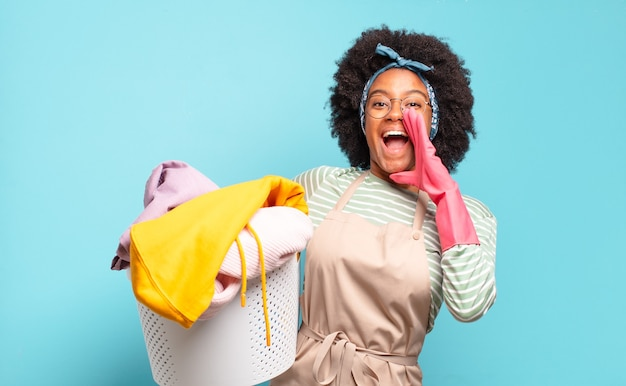 Czarna afro kobieta czuje się szczęśliwa, podekscytowana i pozytywna, krzyczy głośno z rękami przy ustach i woła. koncepcja sprzątania .. koncepcja gospodarstwa domowego