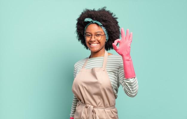 Czarna afro kobieta czuje się szczęśliwa, zrelaksowana i usatysfakcjonowana, okazując aprobatę dobrym gestem, uśmiechając się. koncepcja sprzątania .. koncepcja gospodarstwa domowego