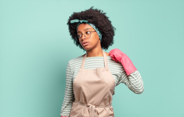 Czarna afro kobieta czuje się zestresowana, niespokojna, zmęczona i sfrustrowana, ciągnie za szyję koszuli, wygląda na sfrustrowaną problemem. koncepcja sprzątania .. koncepcja gospodarstwa domowego
