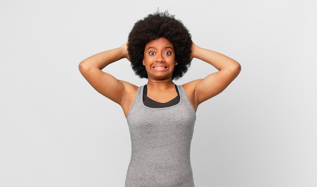 Czarna afro kobieta czuje się zestresowana, zmartwiona, niespokojna lub przestraszona, z rękami na głowie, panikuje z powodu błędu