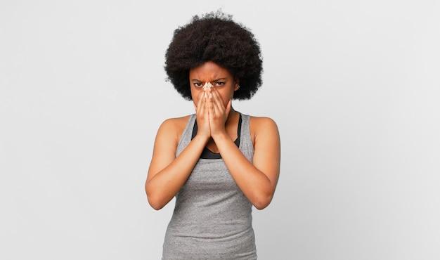Czarna afro kobieta czuje się zmartwiona, pełna nadziei i religijna, modli się wiernie z wyciśniętymi dłońmi, błagając o przebaczenie