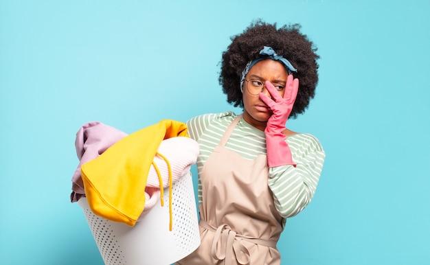 Czarna afro kobieta czuje się znudzona, sfrustrowana i senna po męczącym, nudnym i nudnym zadaniu, trzymając twarz w dłoniach. koncepcja sprzątania .. koncepcja gospodarstwa domowego