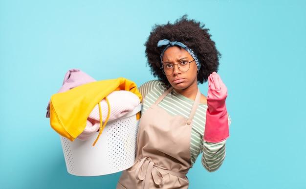 Czarna afro kobieta robi gest kaprysu lub pieniędzy, każe ci spłacić długi! koncepcja sprzątania .. koncepcja gospodarstwa domowego