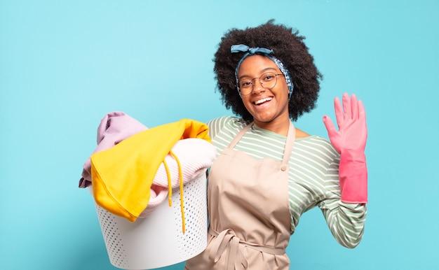 Czarna afro kobieta uśmiecha się radośnie i wesoło, macha ręką, wita i wita lub żegna się. koncepcja sprzątania .. koncepcja gospodarstwa domowego