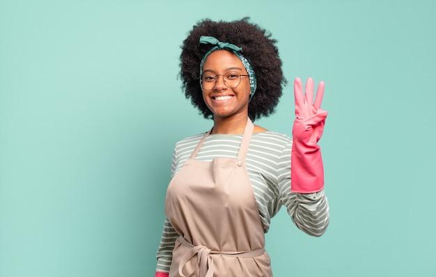Czarna afro kobieta uśmiechnięta i wyglądająca przyjaźnie, pokazująca cyfrę trzy lub trzecią z ręką do przodu, odliczająca. koncepcja sprzątania. koncepcja gospodarstwa domowego