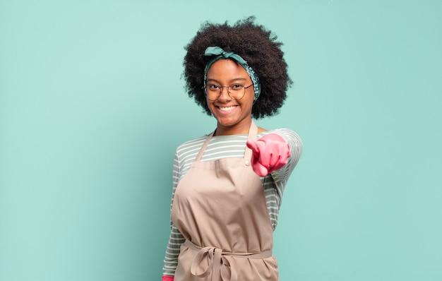 Czarna afro kobieta wskazująca na aparat z zadowolonym, pewnym siebie, przyjaznym uśmiechem, wybiera ciebie