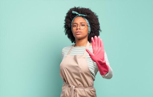 Czarna afro kobieta wyglądająca poważnie, surowo, niezadowolona i zła, pokazująca otwartą dłoń wykonującą gest stop. koncepcja sprzątania. koncepcja gospodarstwa domowego