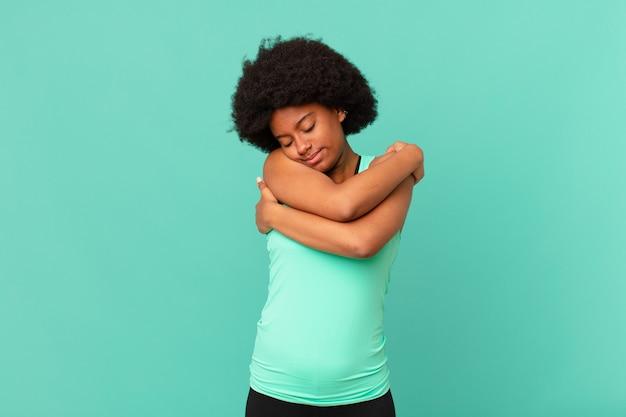 Czarna afro kobieta zakochana, uśmiechnięta, przytulająca się i przytulająca, pozostająca samotna, będąc samolubną i egocentryczną
