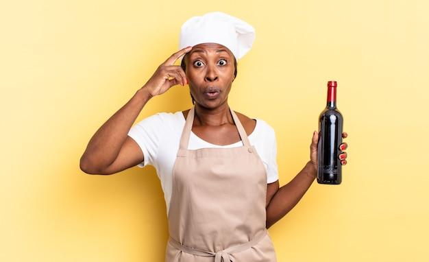 Czarna afro szefowa kuchni wyglądająca na szczęśliwą, zdziwioną i zaskoczoną, uśmiechniętą i uświadamiającą sobie niesamowite i niewiarygodnie dobre wieści. koncepcja butelki wina