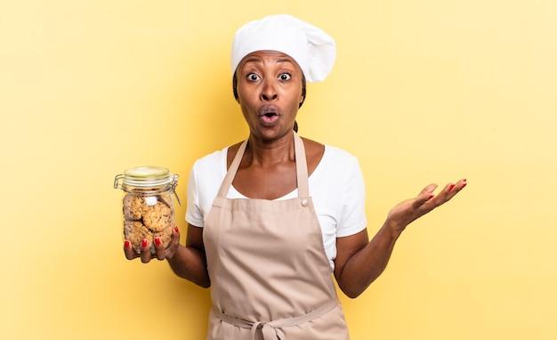 Czarna afro szefowa kuchni z otwartymi ustami i zdumiona, zszokowana i zdumiona niewiarygodną niespodzianką. koncepcja ciasteczek