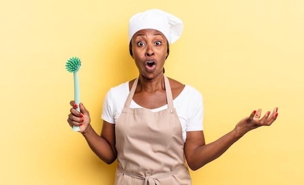 Czarna afro szefowa kuchni z otwartymi ustami i zdumiona, zszokowana i zdumiona niewiarygodną niespodzianką. koncepcja czyszczenia naczyń