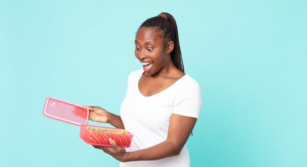 Czarna afroamerykanka dorosła kobieta trzyma tupperware