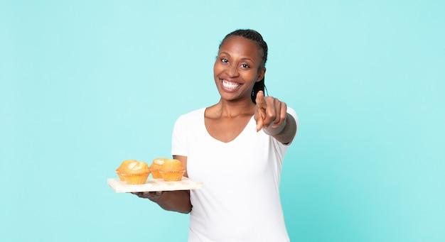 Czarna afroamerykanka dorosła kobieta trzymająca tacę z babeczkami