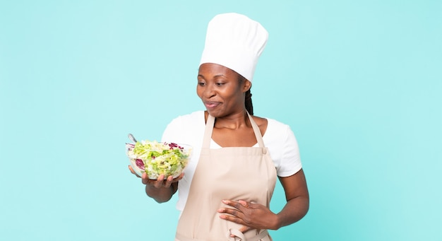 Czarna afroamerykańska dorosła kobieta kucharz trzyma sałatkę