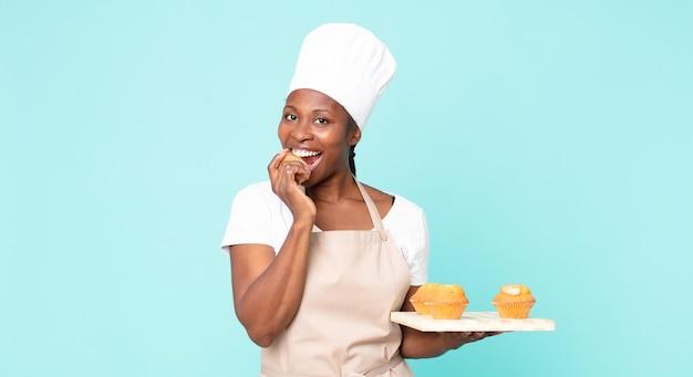 Czarna afroamerykańska dorosła kobieta szefa kuchni trzymająca tacę z babeczkami