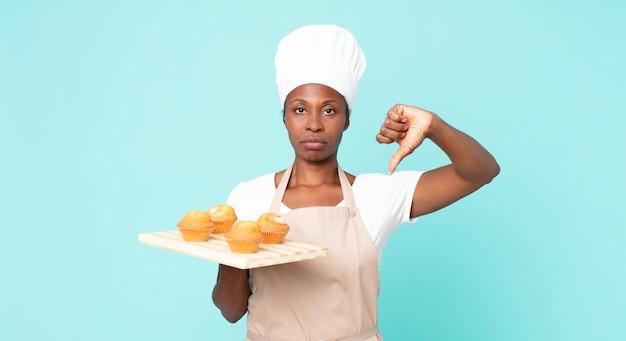 Czarna afroamerykańska dorosła kobieta szefa kuchni trzymająca tacę z babeczkami;