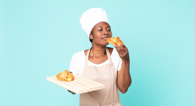 Czarna afroamerykańska dorosła kobieta szefa kuchni trzymająca tacę z rogalikami