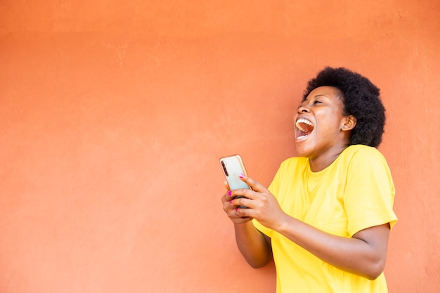Czarna afrykańska kobieta czuje się podekscytowana po otrzymaniu dobrych wiadomości z telefonu komórkowego