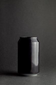 Czarna aluminiowa puszka na czarnym tle. makieta.