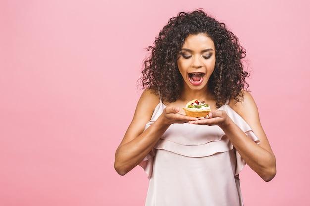 Czarna amerykańska afrykańska szczęśliwa kobieta z kręconymi włosami afro robiąca bałagan, jedząc ogromny fantazyjny deser na różowym tle. jedzenie babeczki.