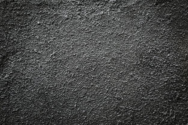 Czarna asfaltowa ziarnista ściana.