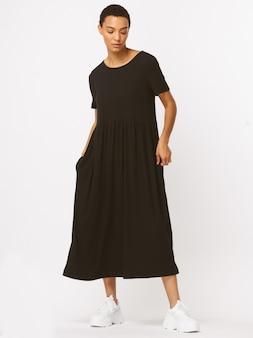 Czarna, bezkształtna sukienka, długie rękawy, czarne wysokie buty. smukłe ciało, jedwabna skóra. biały uśmiech, słodka buźka, fryzura brunetki.